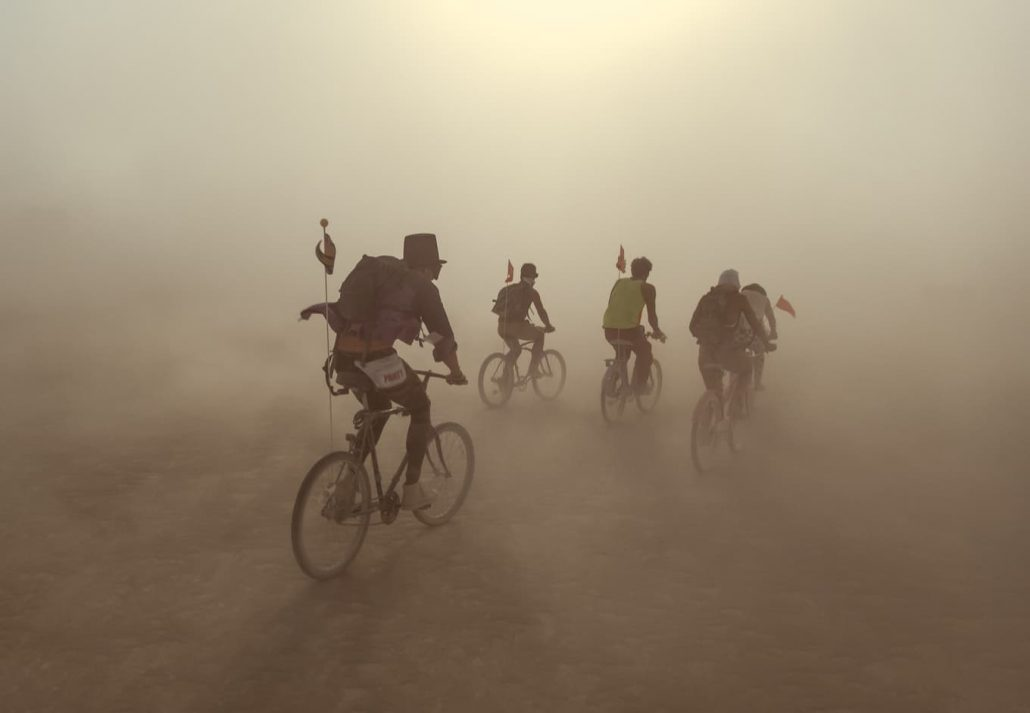 Group of people riding on bikes in dust storm