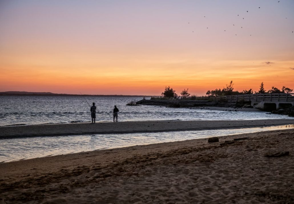 Two men fishing on the bay at sunset on Sandy Hook along the Jersey shore.