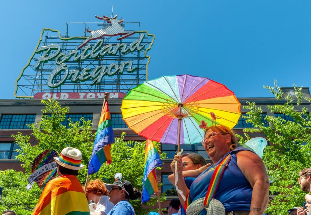 The crowd moves under the famous Portland Sign during the 2018 Pride Parade through the streets of downtown Portland.